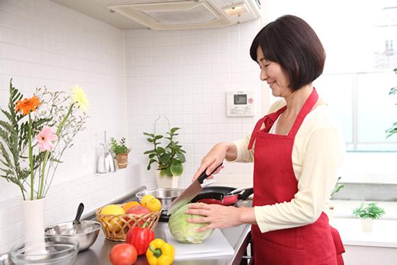 おいしい野菜を使って料理する女性