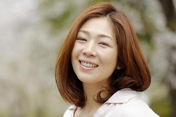 桜の前で笑顔の女性