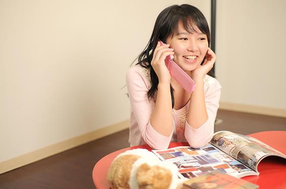 チラシを見ながら電話をする女性