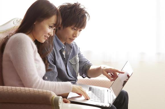 パソコンをみるカップル