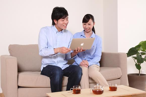 パソコンをソファで見るカップル